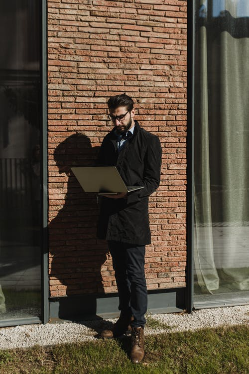 파란색 재킷과 갈색 벽돌 벽 옆에 서있는 검은 바지를 입은 남자