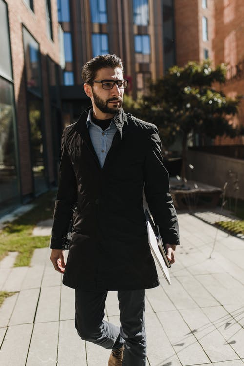 Photo of a Man in a Black Coat Walking while Looking Away