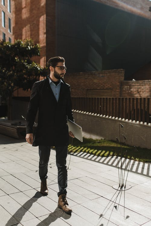 Photo of a Man in a Black Coat Walking while Carrying His Laptop