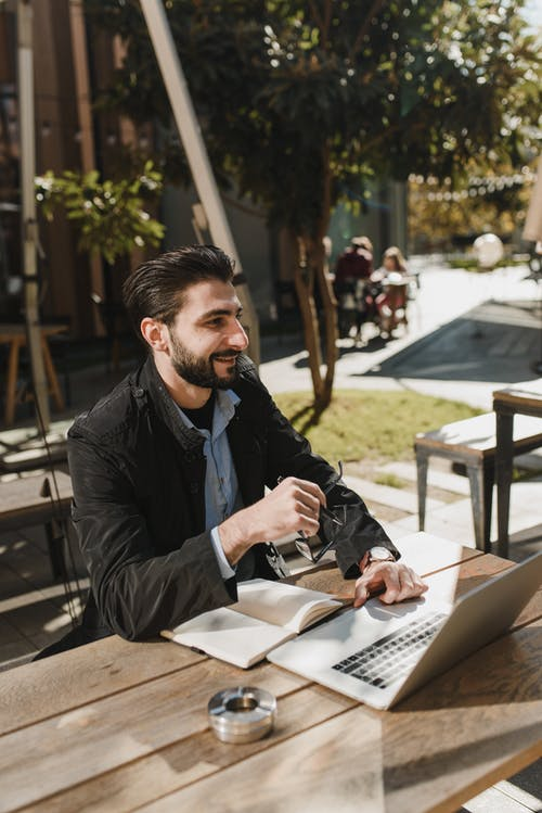 Smiling ethnic entrepreneur in trendy clothes sitting at wooden table with notebook and browsing laptop while working on street in sunny day