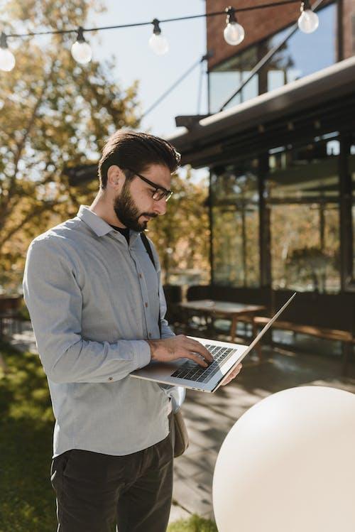 Homem De Camisa Branca Usando Macbook Pro
