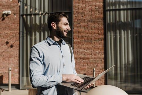 Cheerful entrepreneur using laptop on street