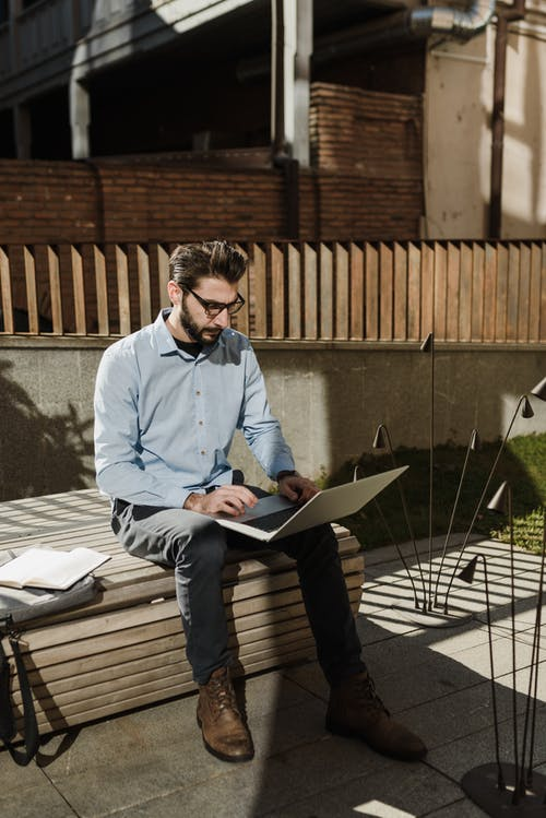 Pria Berbaju Biru Dan Macbook Memegang Celana Hitam