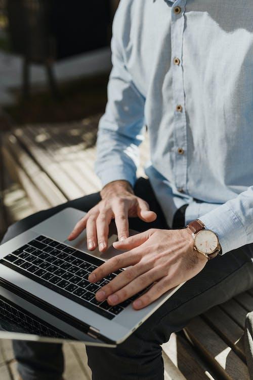 Orang Dengan Kemeja Biru Dan Celana Hitam Menggunakan Macbook Pro