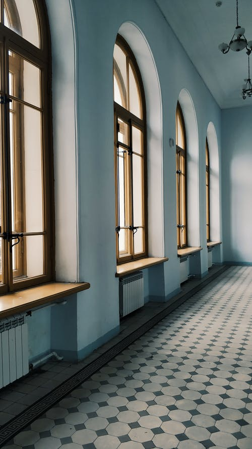 Interior design of spacious light hallway with arched windows and tiled floor in daylight