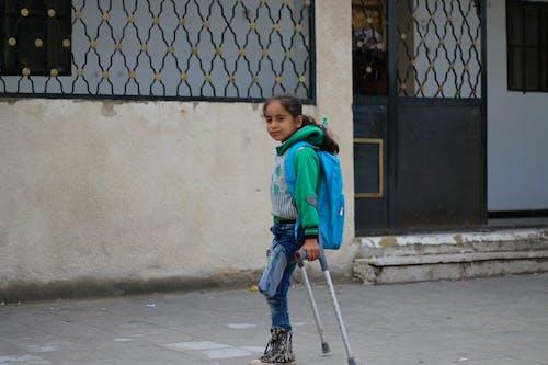 Ethnic amputated girl walking on crutches