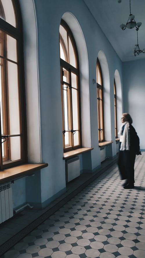 Woman standing in spacious hallway and looking out window