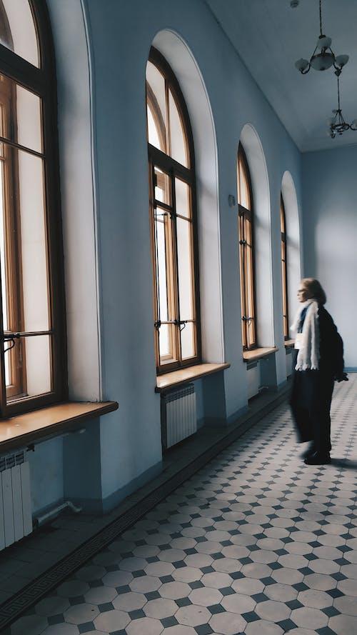 広々とした廊下に立って窓の外を見ている女性