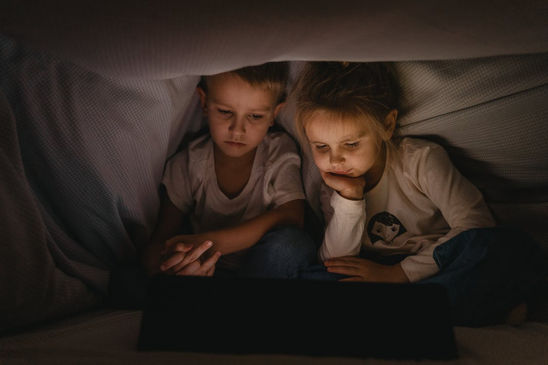 Boy and Girl Lying on Bed