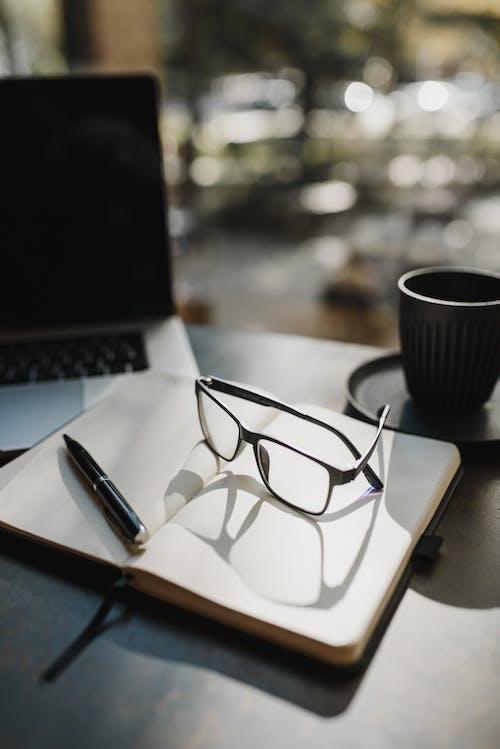 黒のペンの横にある白い紙に黒のフレームの眼鏡