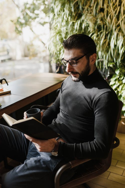 Man Sitting on Chair Reading Book