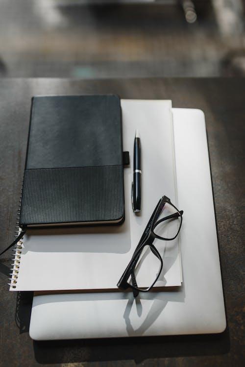 白いノートに黒いフレームの眼鏡
