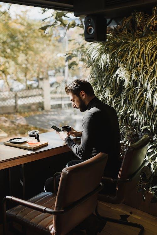 Homem De Camisa Preta De Manga Comprida Sentado Na Cadeira De Couro Preto