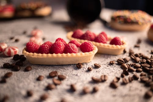 Delicious fresh raspberry tartlets placed on table amidst aromatic coffee beans and sweets