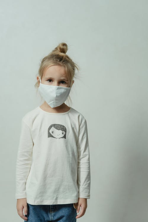 Girl in White Long Sleeve Shirt Wearing White Face Mask