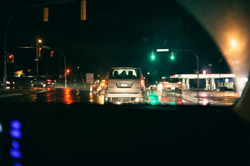 Various modern cars driving on road at night