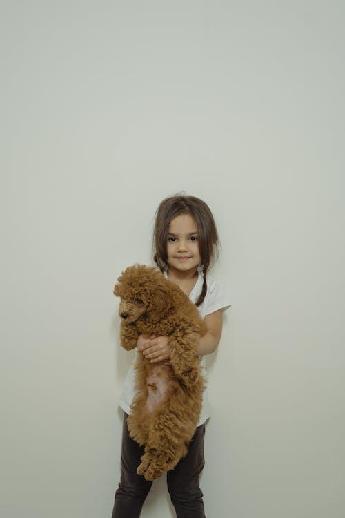 Girl in White Tank Top Holding Brown Teddy Bear