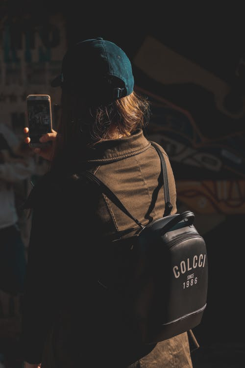 Back view of anonymous female in casual clothes and cap taking photo of picture on wall on smartphone on street in evening