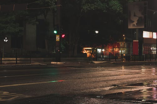 Empty asphalt road traffic lights and bus stop in modern street in big city at night
