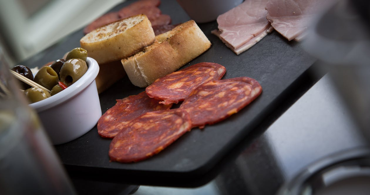 Meat and Bread Slices on Top of Black Table