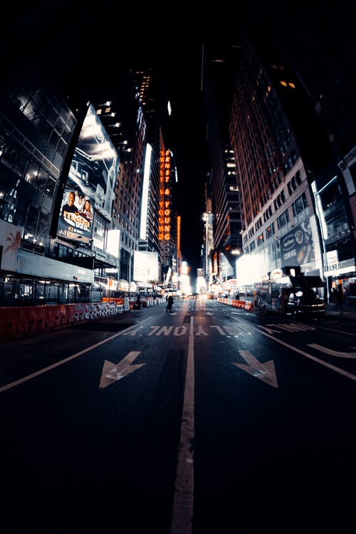 Modern glowing city street with road between buildings