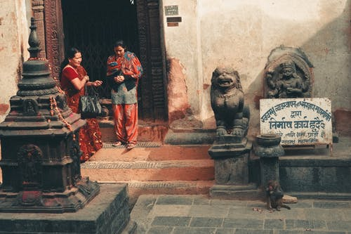 Nepali women in traditional clothes standing near Buddhist temple