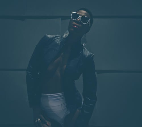 Confident black female model in trendy outfit and sunglasses and in earrings standing in dark near uneven wall