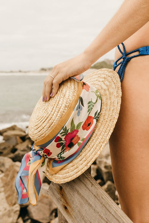 Woman in Blue and White Floral Bikini Wearing Brown Sun Hat