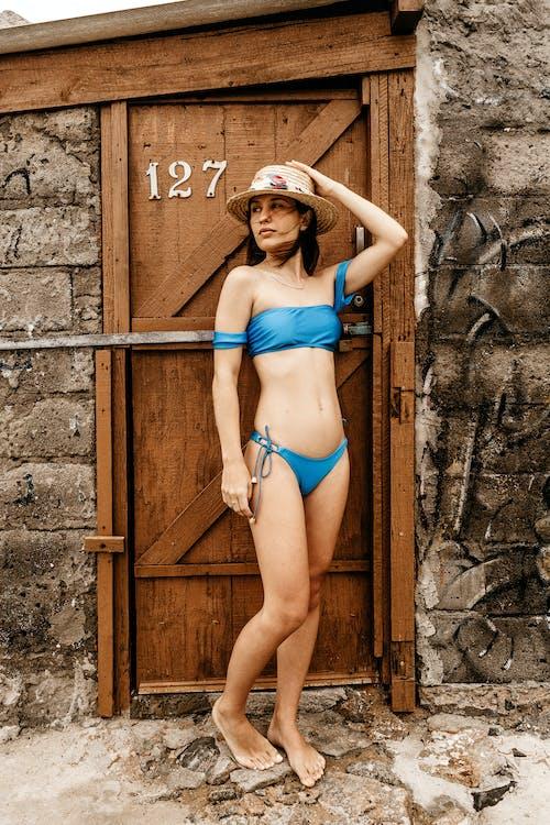 Woman in Blue Bikini Leaning on Brown Wooden Door