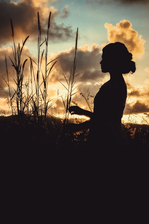 Unrecognizable female recreating in field at sundown