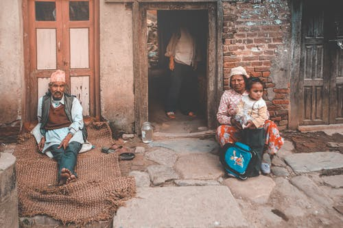 Ethnic people sitting on old street near old house in countryside