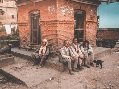 Full body of elderly ethnic local men in rustic clothes sitting near old brick house on shabby street in Nepalese village