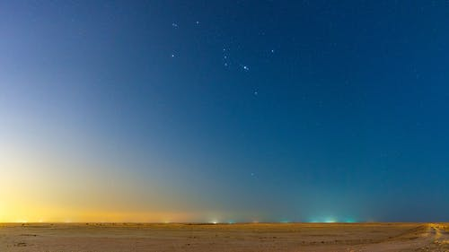 Picturesque scenery of stars shining in cloudless sunset sky over endless sandy desert