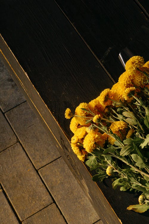 Yellow Flowers on Brown Wooden Table