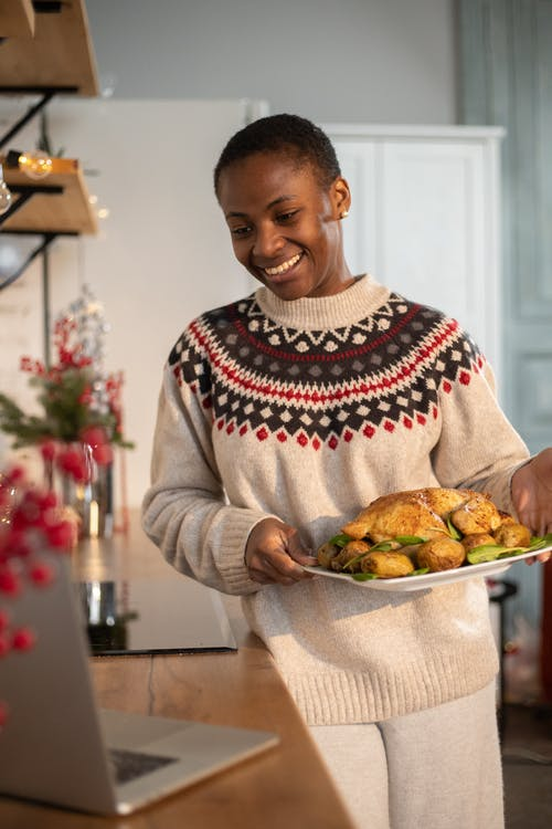 Woman in Brown Sweater Holding Tray With Food