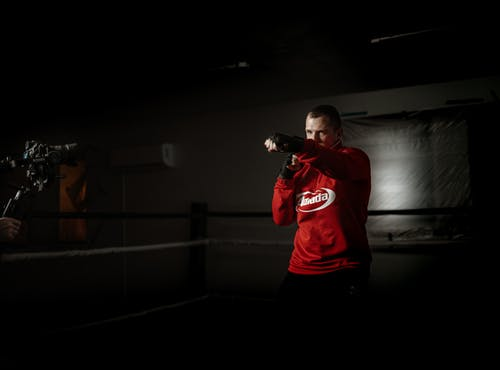 Powerful male athlete in sportswear practicing boxing hits in ring against crop anonymous partner recording video on photo camera