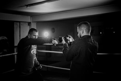 Powerful boxer showing punch technique against friend with camera