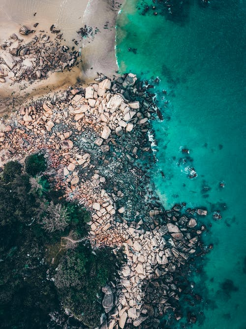 Picturesque seascape with turquoise water and stones near sandy shore