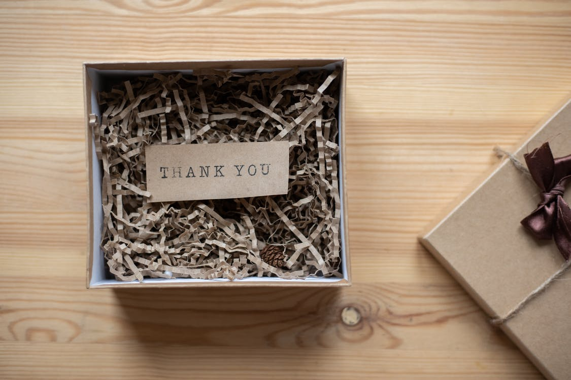 Top view of opened carton present box with small postcard with Thank You inscription and paper stuffing on wooden table