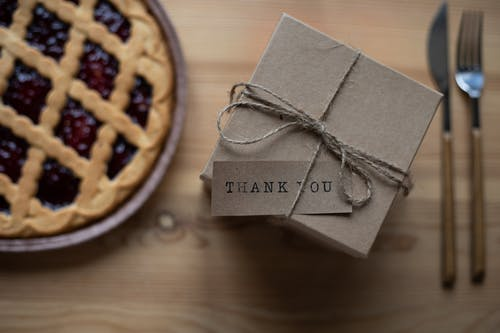 Cardboard present box with postcard on table