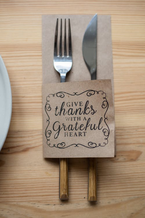 Top view of metal fork and knife in paper cover decorated with Give Thanks With A Grateful Heart inscription placed on wooden table