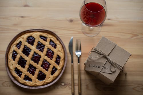 Delicious pie near glass of wine and gift box on table