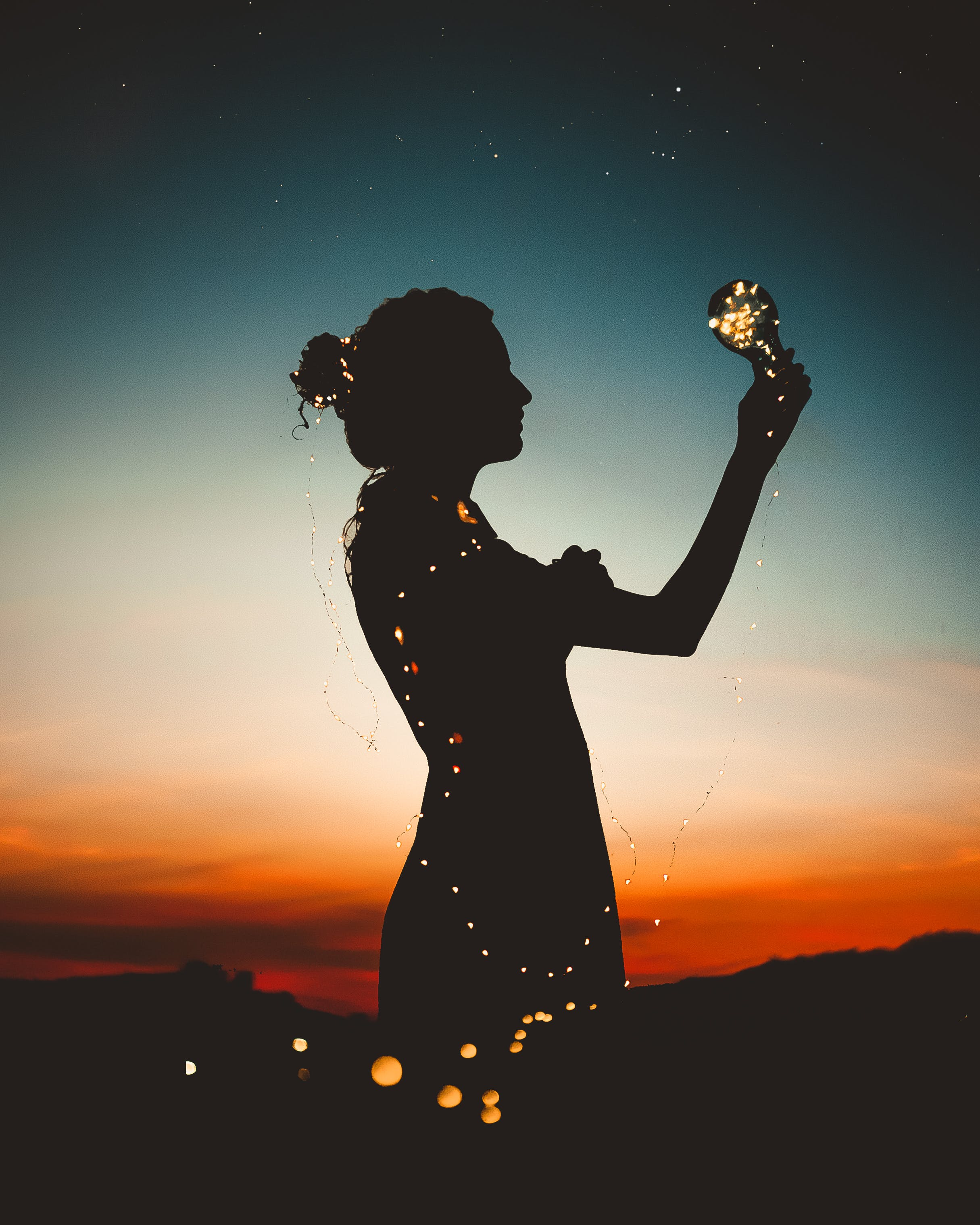Woman Holding Lit-up Light String Silhouette Photography