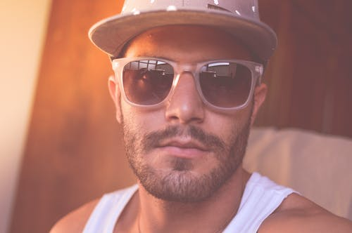 Man Wearing White Tank Top and Sunglasses Taking Close-up Selfie