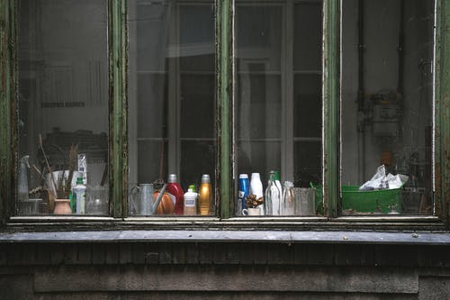 White and Blue Plastic Bottles on Window