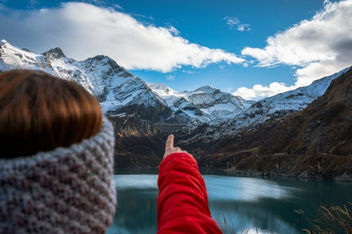 Person in Red and White Pants Near Lake and Snow Covered Mountain