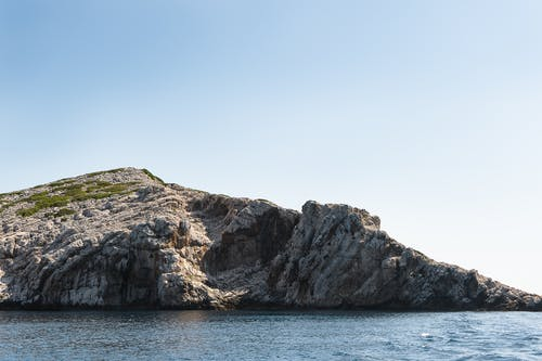 Gray Rock Formation on Sea Under Blue Sky