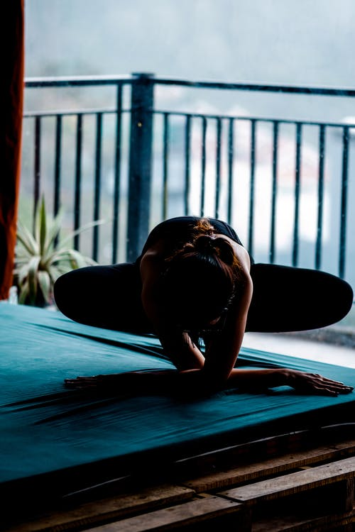 Full body of sportive faceless woman in activewear performing yoga asana while training at home on veranda near metal fence