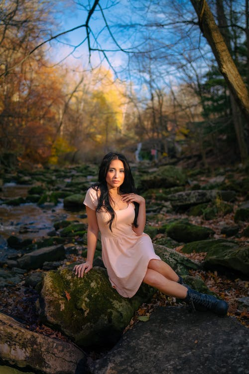Charming model sitting on rock in forest