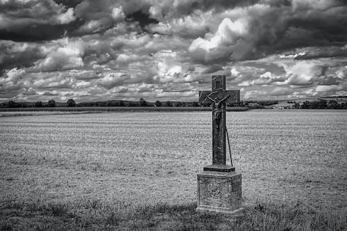 Grayscale Photo of Cross on Grass Field